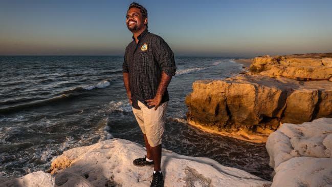 Man standing on rock by ocean