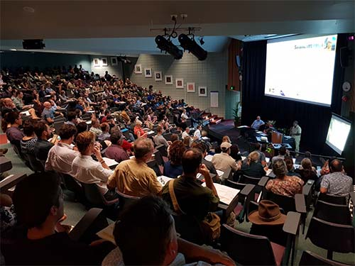Speaker presenting to people in a theatre room